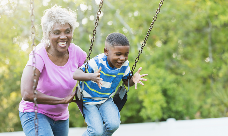 Retired woman pushing boy on swing