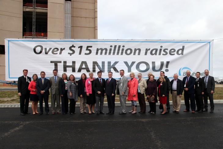 Group posing in front of a thank you banner