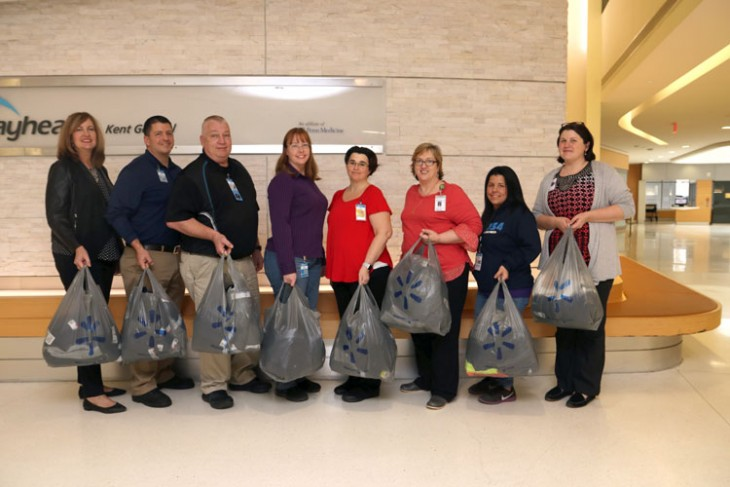 Bayhealth employees holding bags filled with clothing from Walmart donation